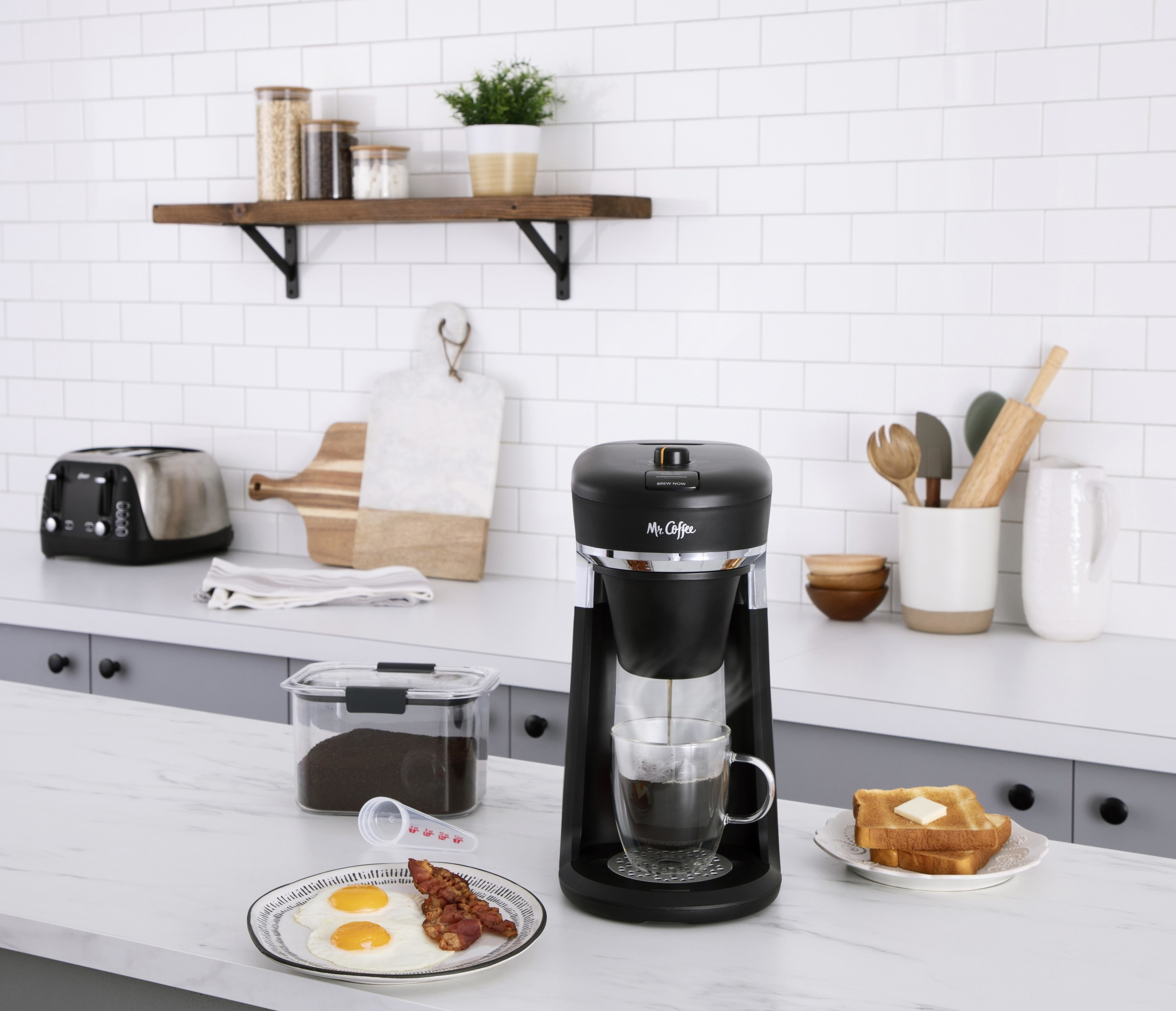 The coffee maker surrounded by breakfast in a kitchen