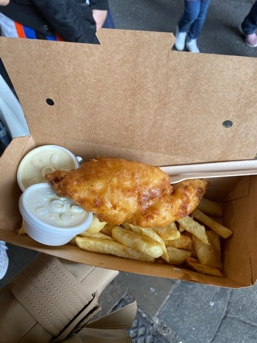 A cardboard box is open to reveal a piece of fried fish on top of fries with two closed containers of sauce