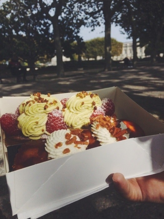A hand holds a box full of pastries topped with intricate and colorful frosting and raspberries, in the background is a park with trees