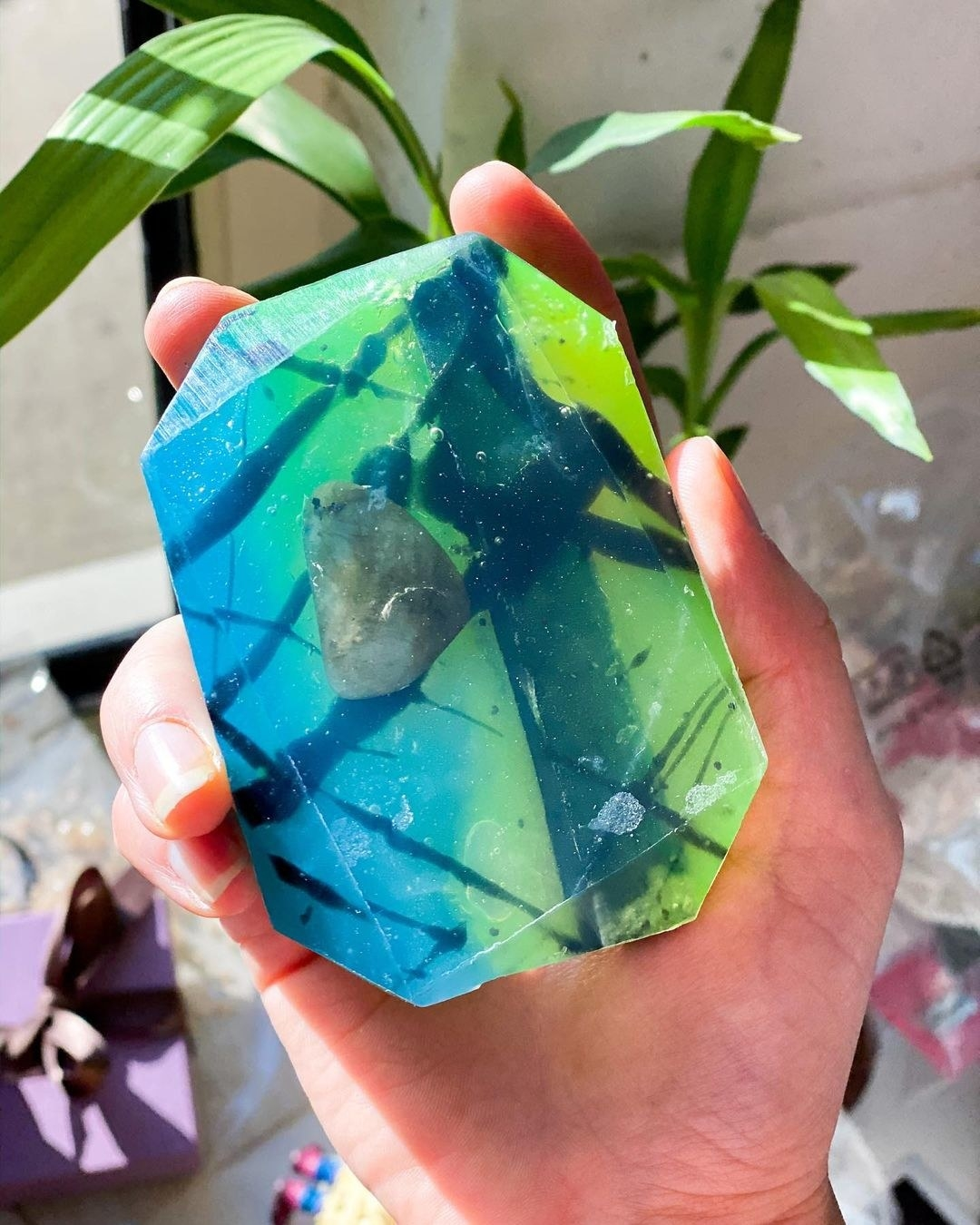 hand holding the palm-sized translucent blue and green bar, with a crystal stone in the center