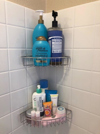 A reviewer's photo of the silver caddies holding body wash, shampoo, and other products