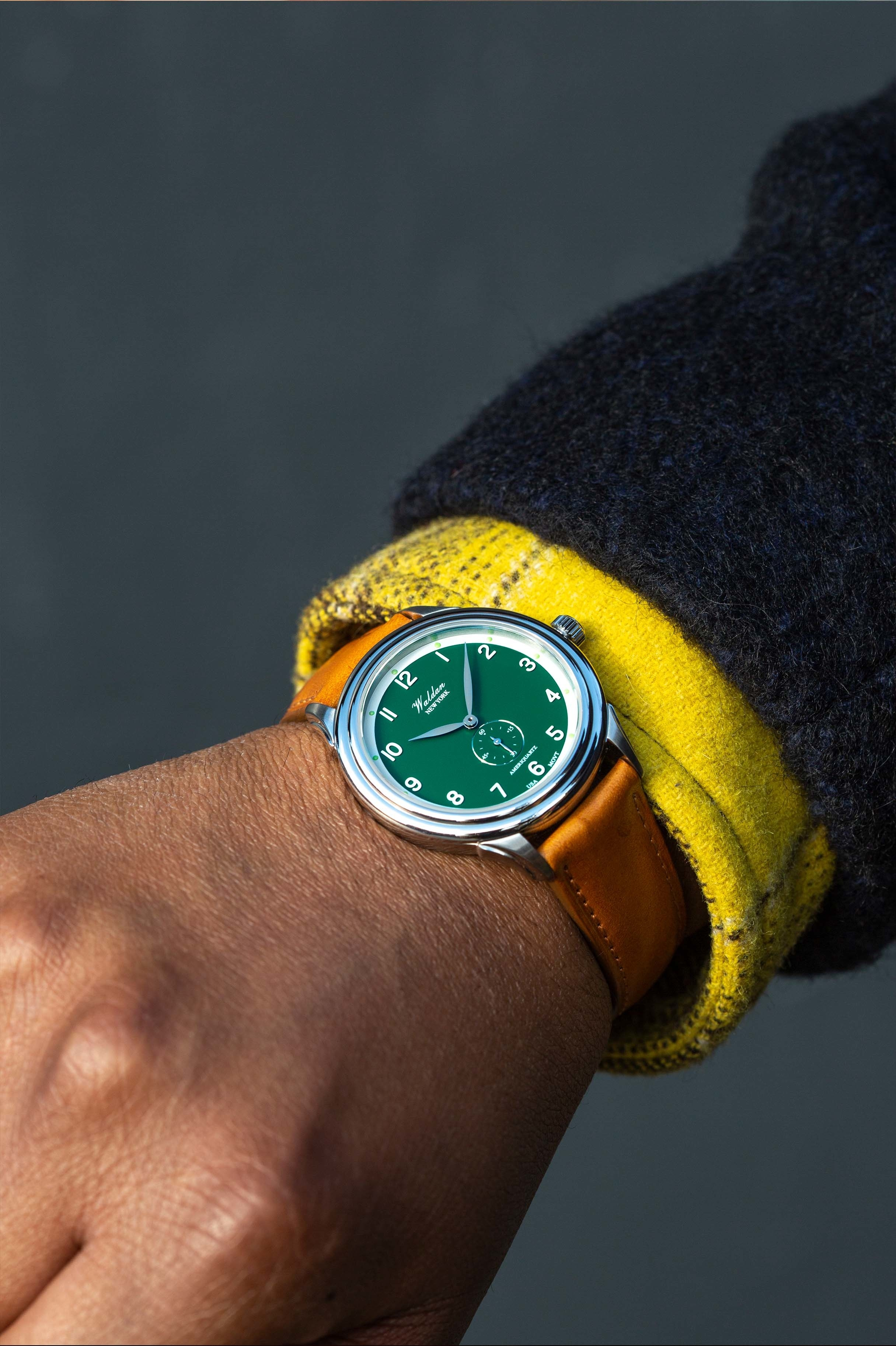 a model wearing a watch with a green face and brown leather band