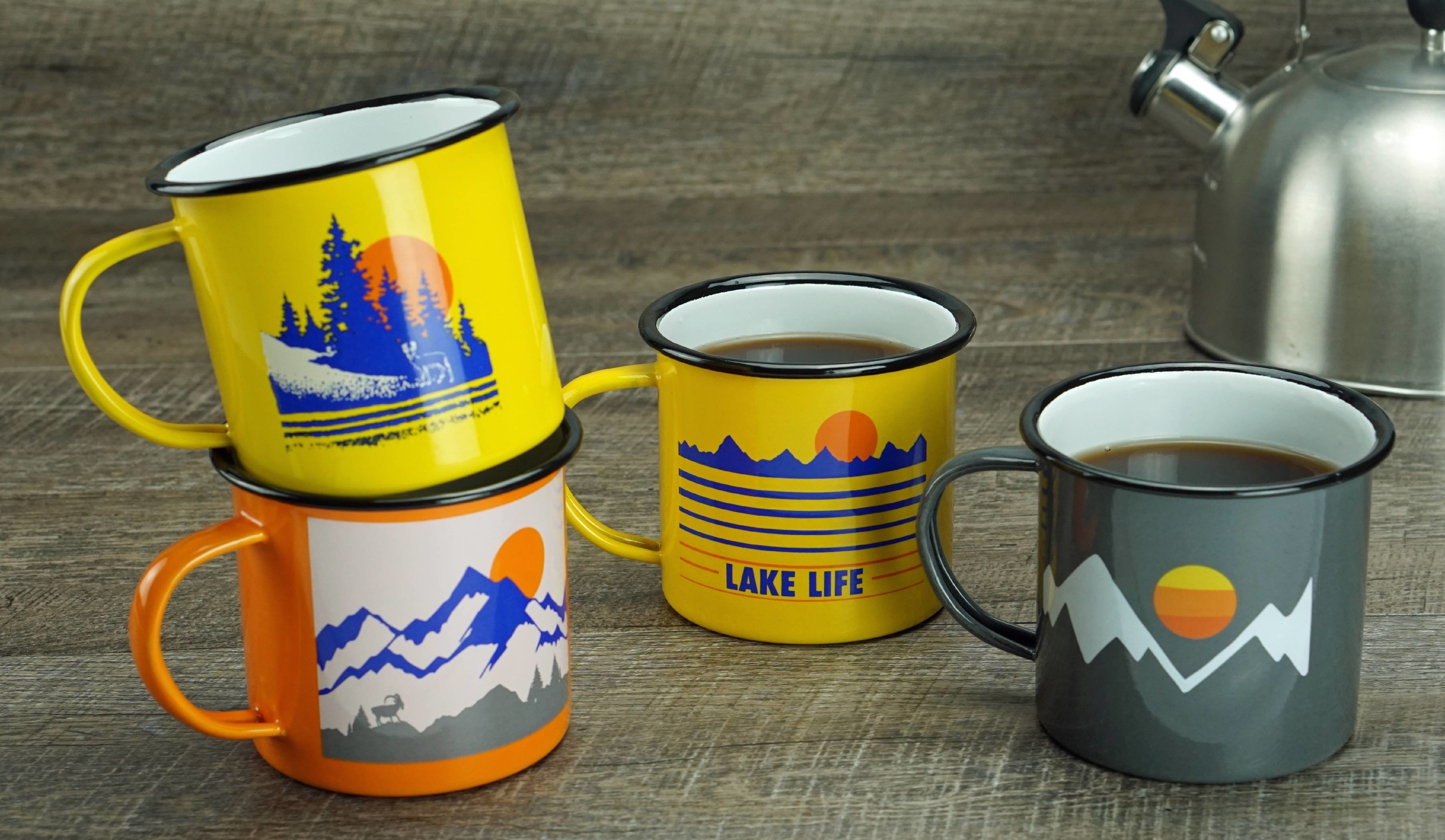 a set of mugs in yellow, orange, and gray with mountain designs on each