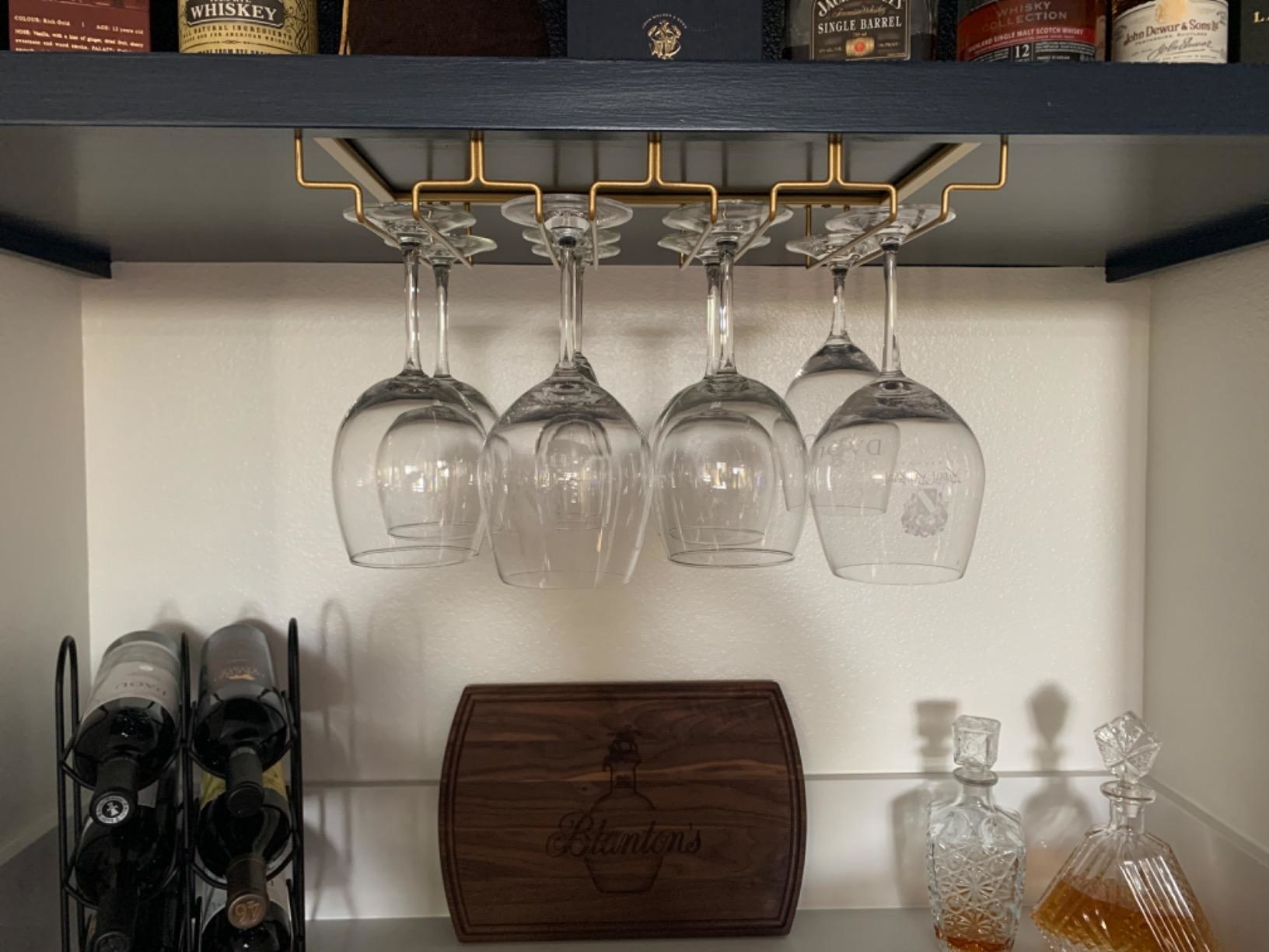 A reviewer's photo of a gold stemware organizer holding eight wine glasses