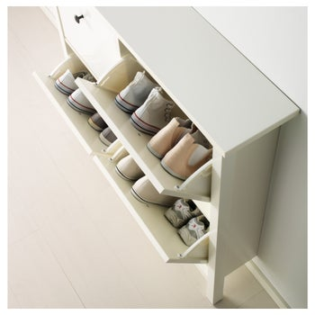 The white cabinet with two drawers open revealing shoes