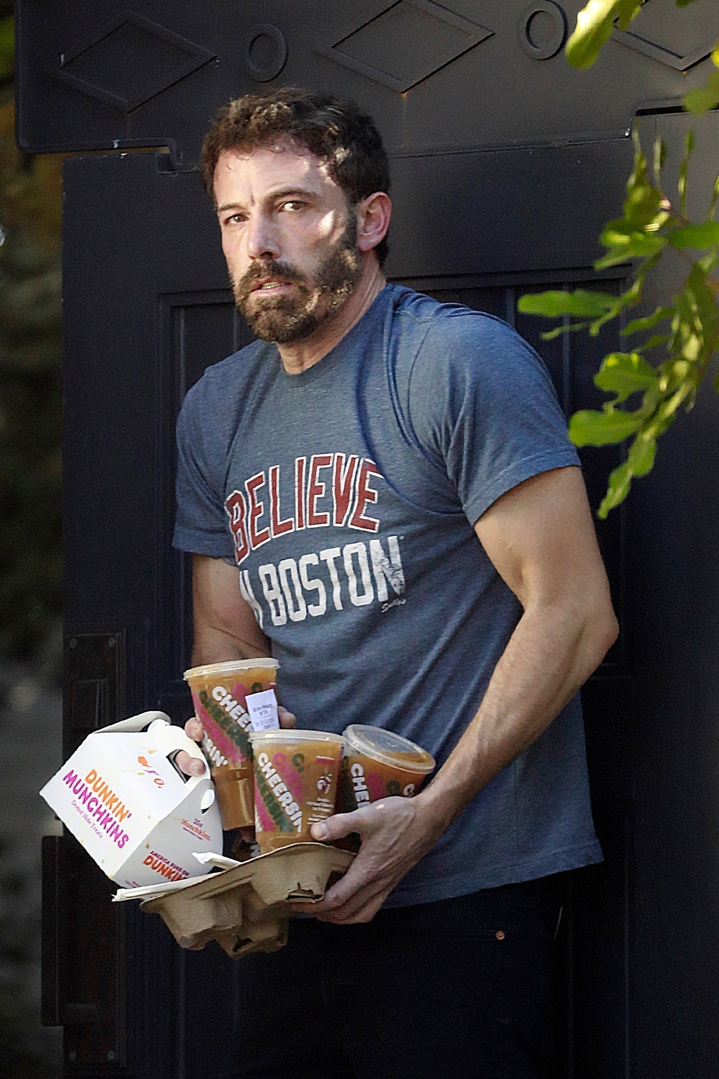 Ben Affleck, on another day, balances several iced coffees and a box of donut holes