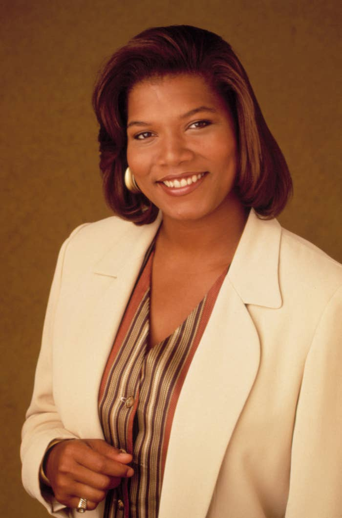 "Queen Latifah is posing in a promotional photo for ""Living Single"" while wearing a neutral tone blazer and V-neck bluse"