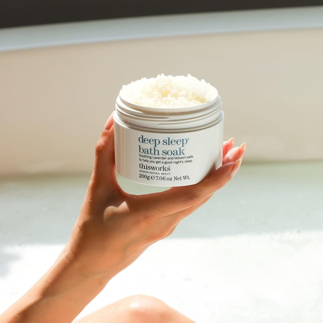 A person holding up a jar of the bath soak, bathed in sunlight