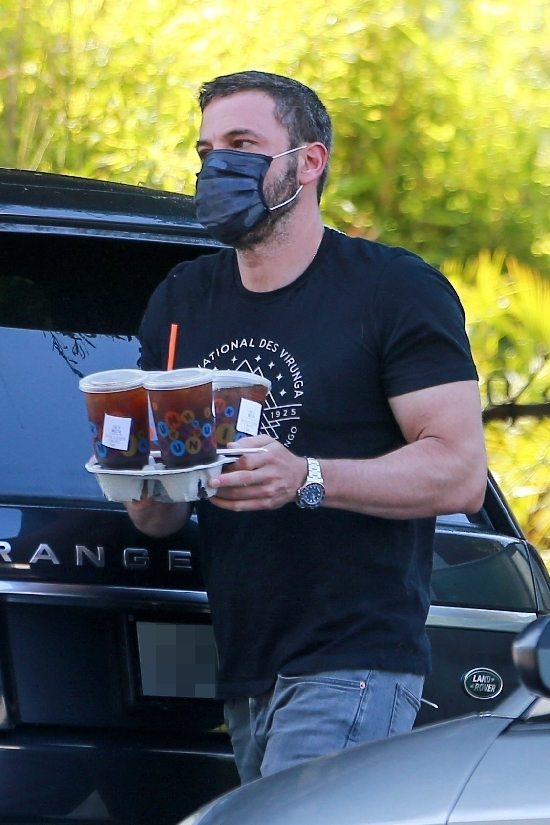 Ben walks, while wearing a face mask, and carries ice beverages in a to-go carrier