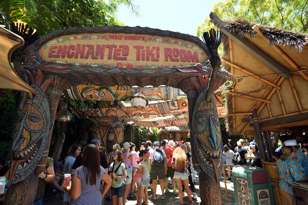 A photo of the outside of the Enchanted Tiki Room during the day with a crowd