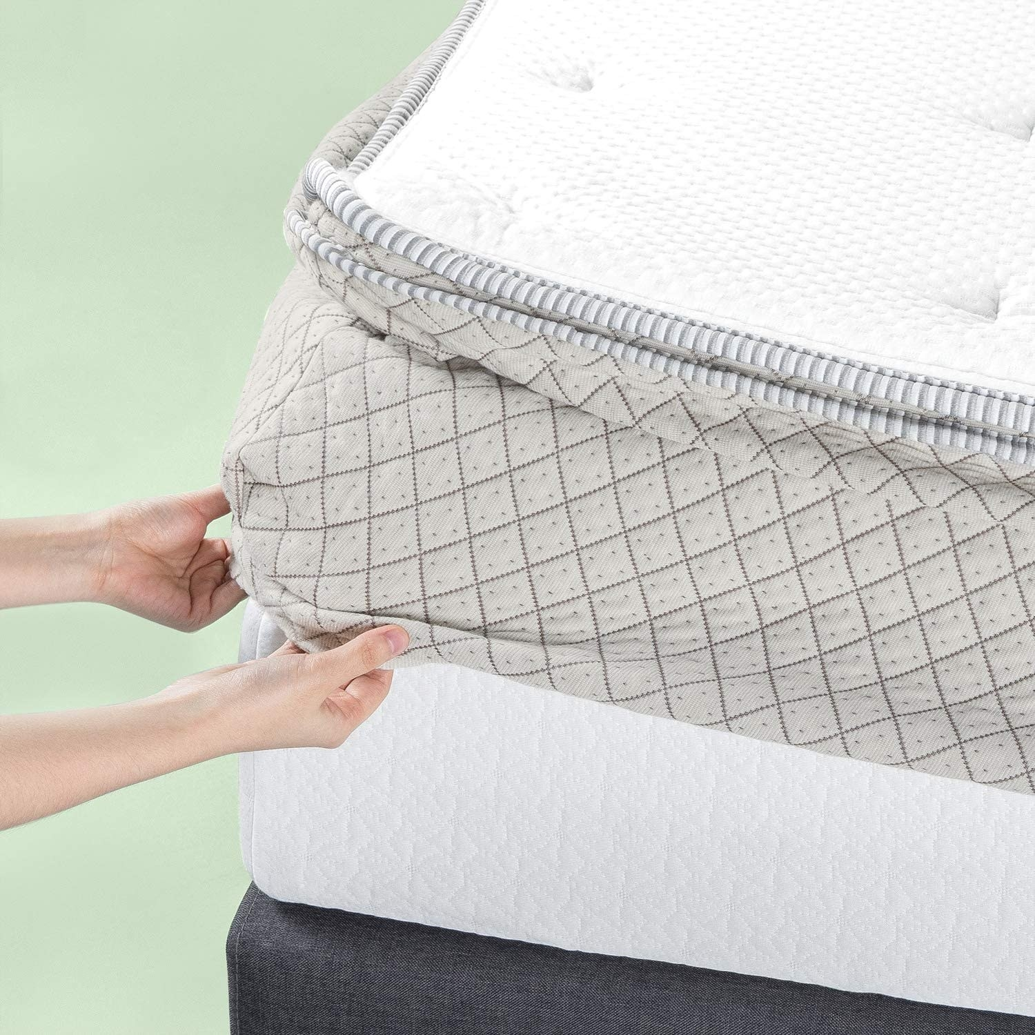 hands putting one corner of the pad onto a mattress