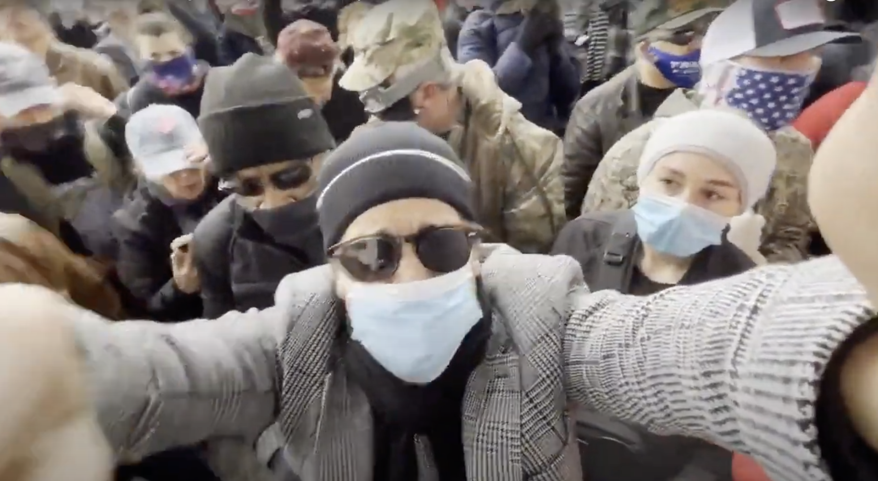 In a video screenshot, Brandon Straka, wearing a beanie, sunglasses, face mask, and jacket, looks into the camera amid a crowd of people