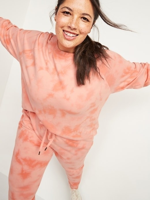 a model in pink tie dye sweatshirt and joggers