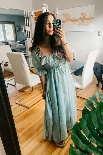 A reviewer wearing the ruffled short-sleeve dress in mint green