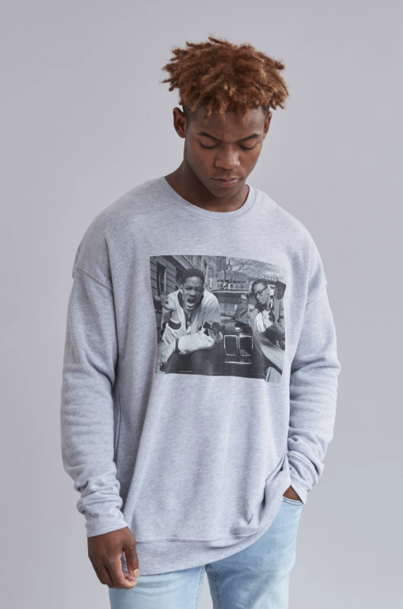model wearing the gray sweatshirt with a black and white image of Will and Jazz on the front