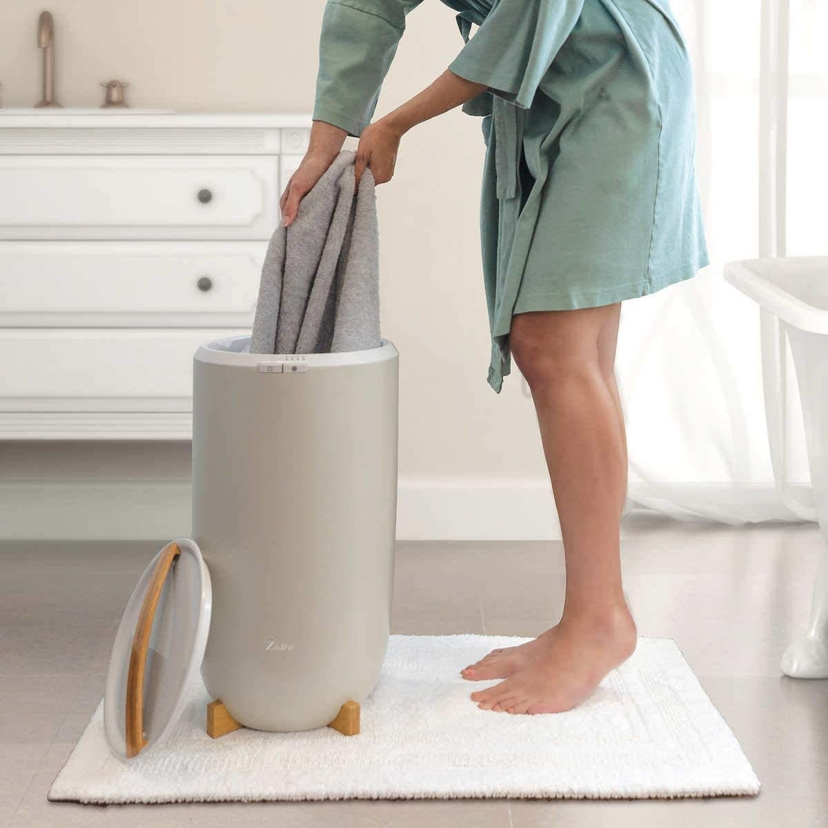 The circular-shaped bin in grey with a lid and wood handle