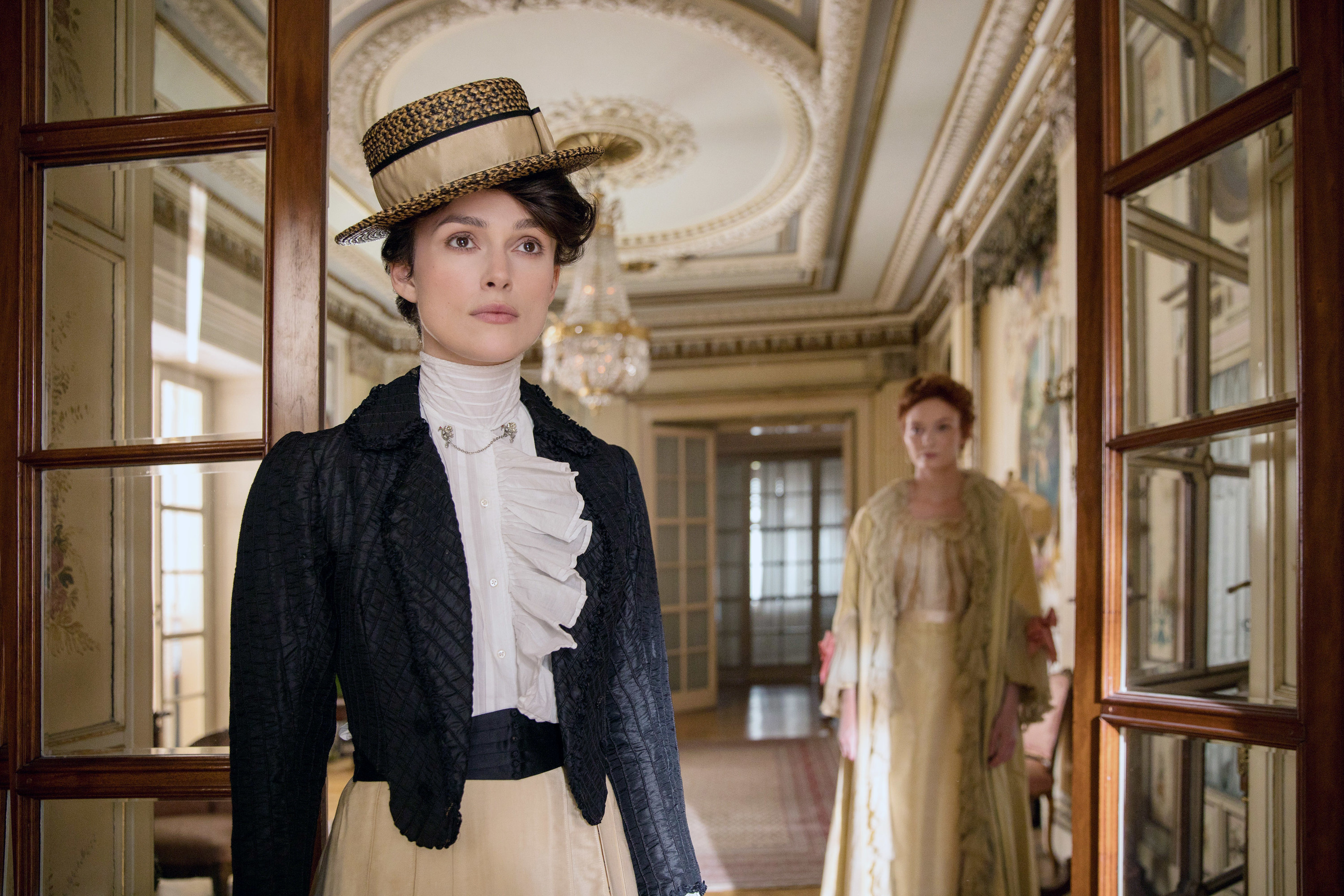 Keira Knightley stands in the foreground with Eleanor Tomlinson in the background in the 2018 film Colette