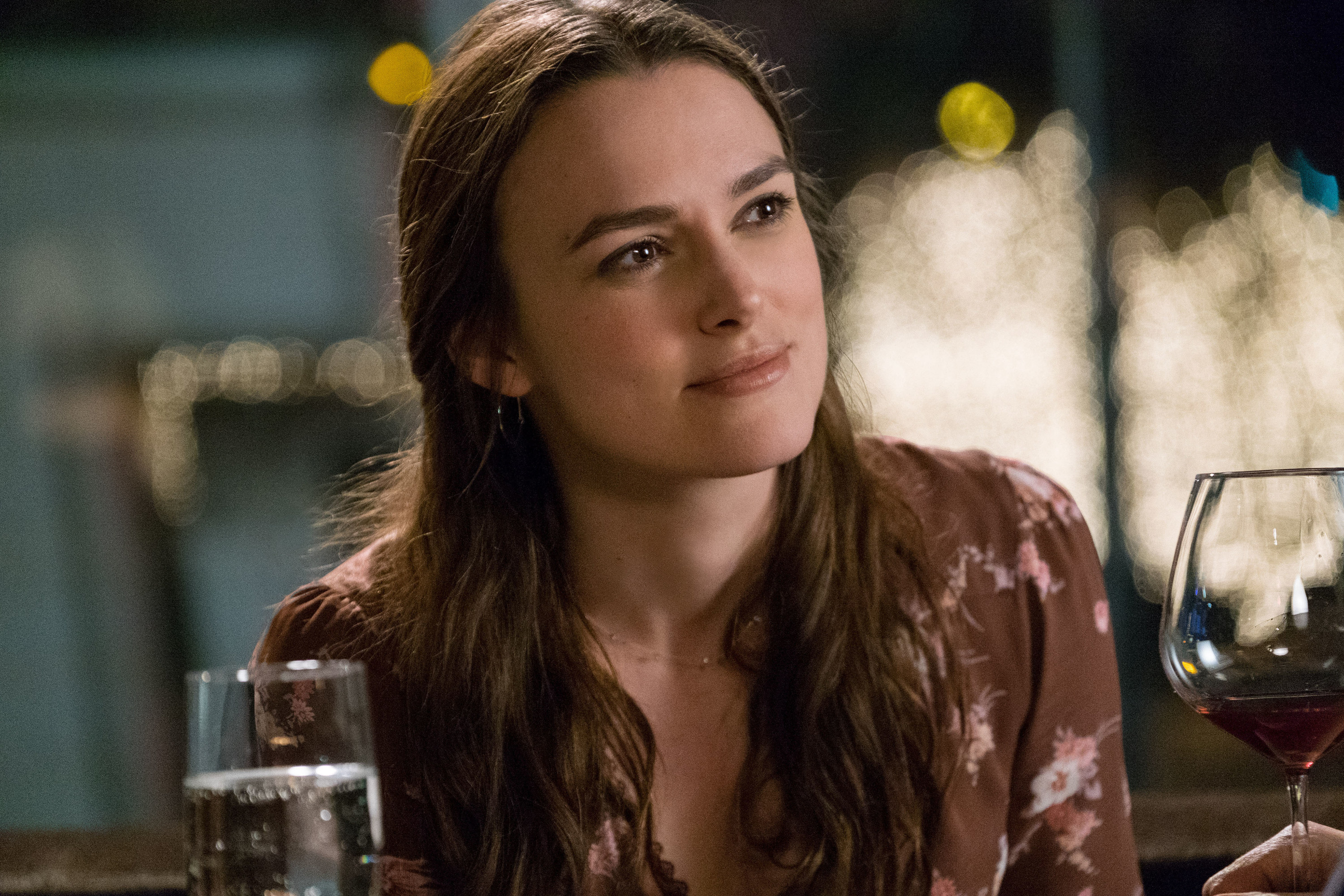 Keira Knightley sits in front of two glasses in the 2016 film Collateral Beauty