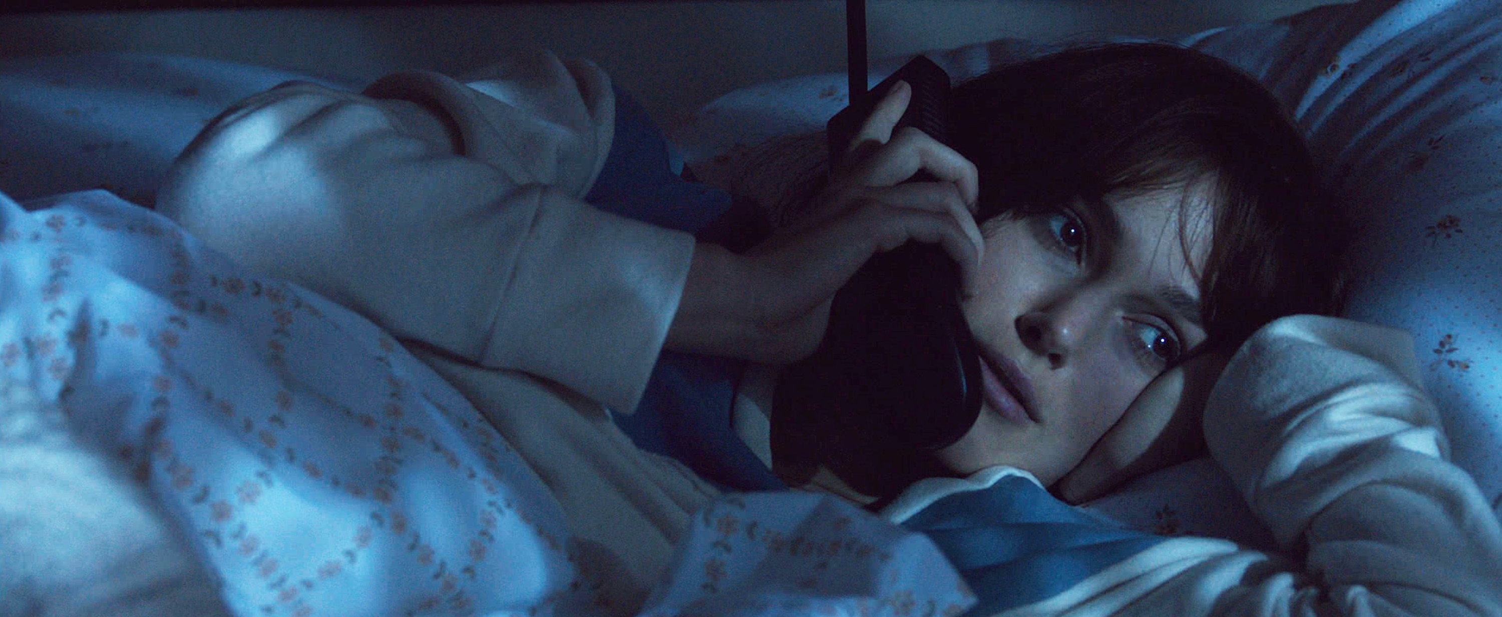 Keira Knightley talks on the phone in bed in the 2015 film Everest