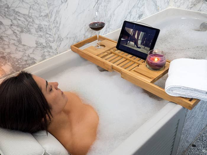 A person lounging in a bubble bath while watching something on a tablet that is sitting on the bathtub tray