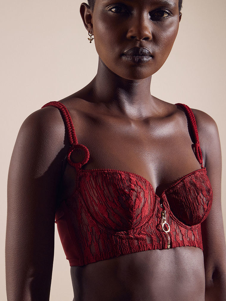 a model in a red lace bustier with a gold zipper down the middle