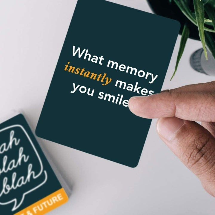 """Model holding card that reads """"What memory instantly makes you smile?"""""""