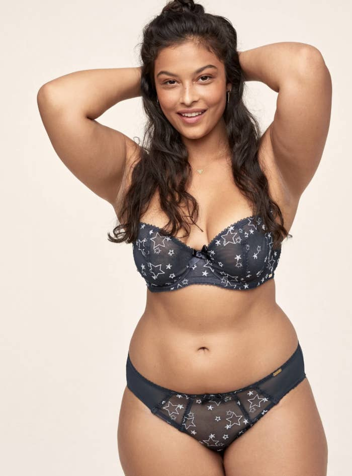 a model in a dark blue unlined bra and underwear with star accent son it