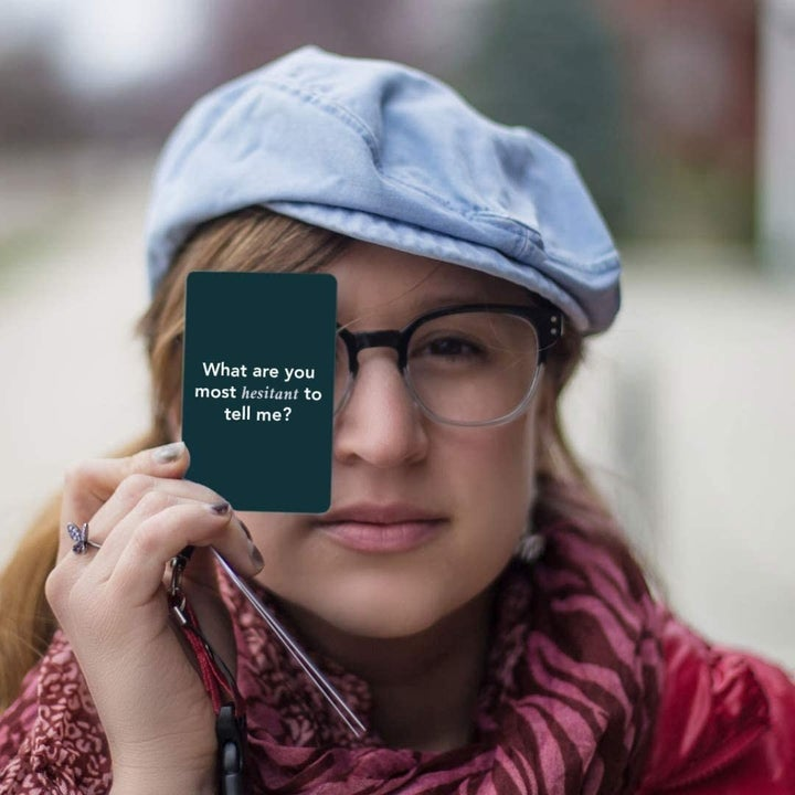 """Model holding card reading """"What are you most hesitant to tell me?"""""""