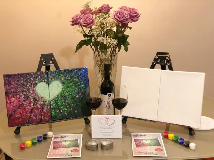 Two easels and paint supplies on table with wine glasses