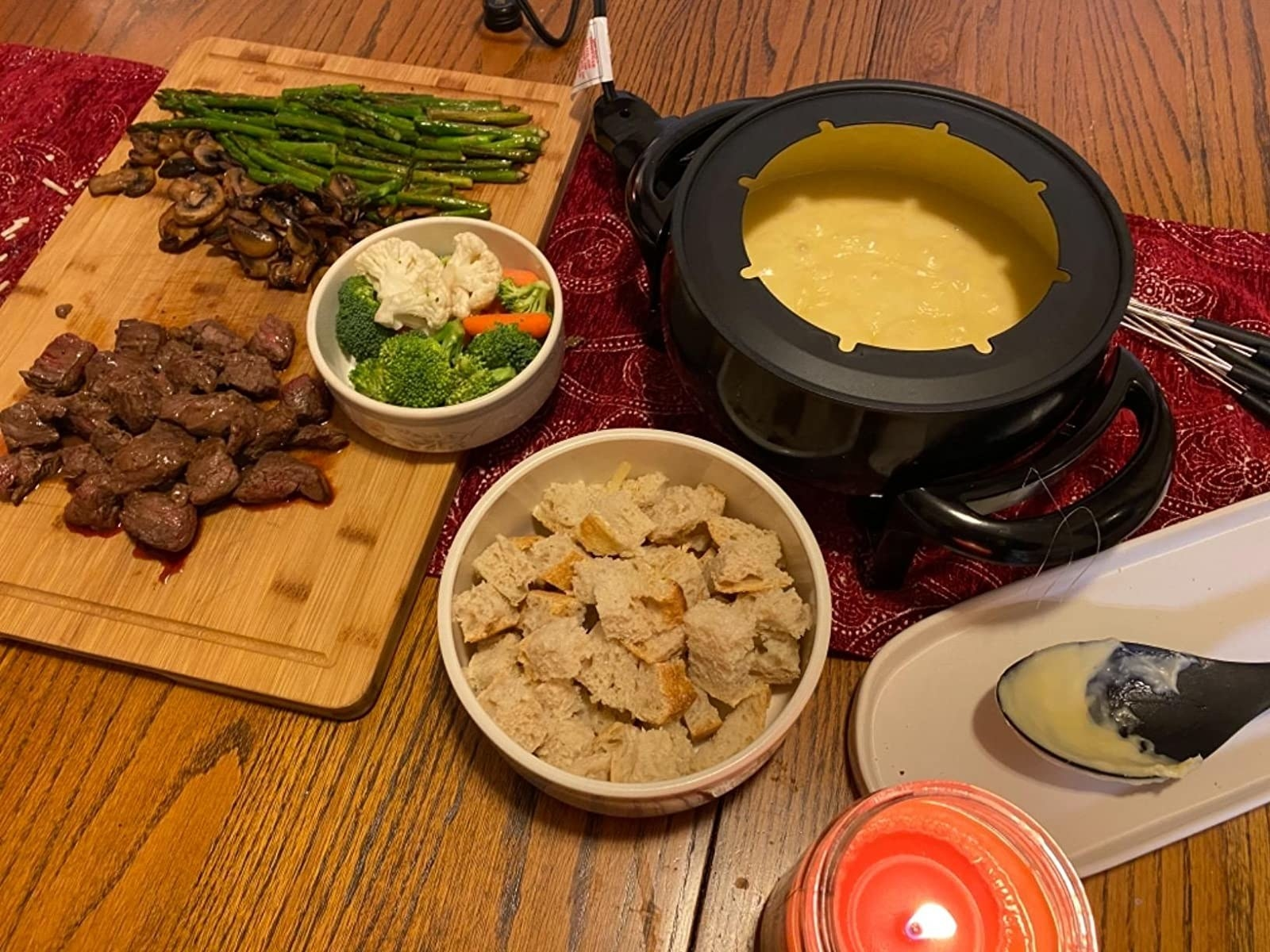 Reviewer photo of fondue poe with melted cheese and various meats, veggies, and bread