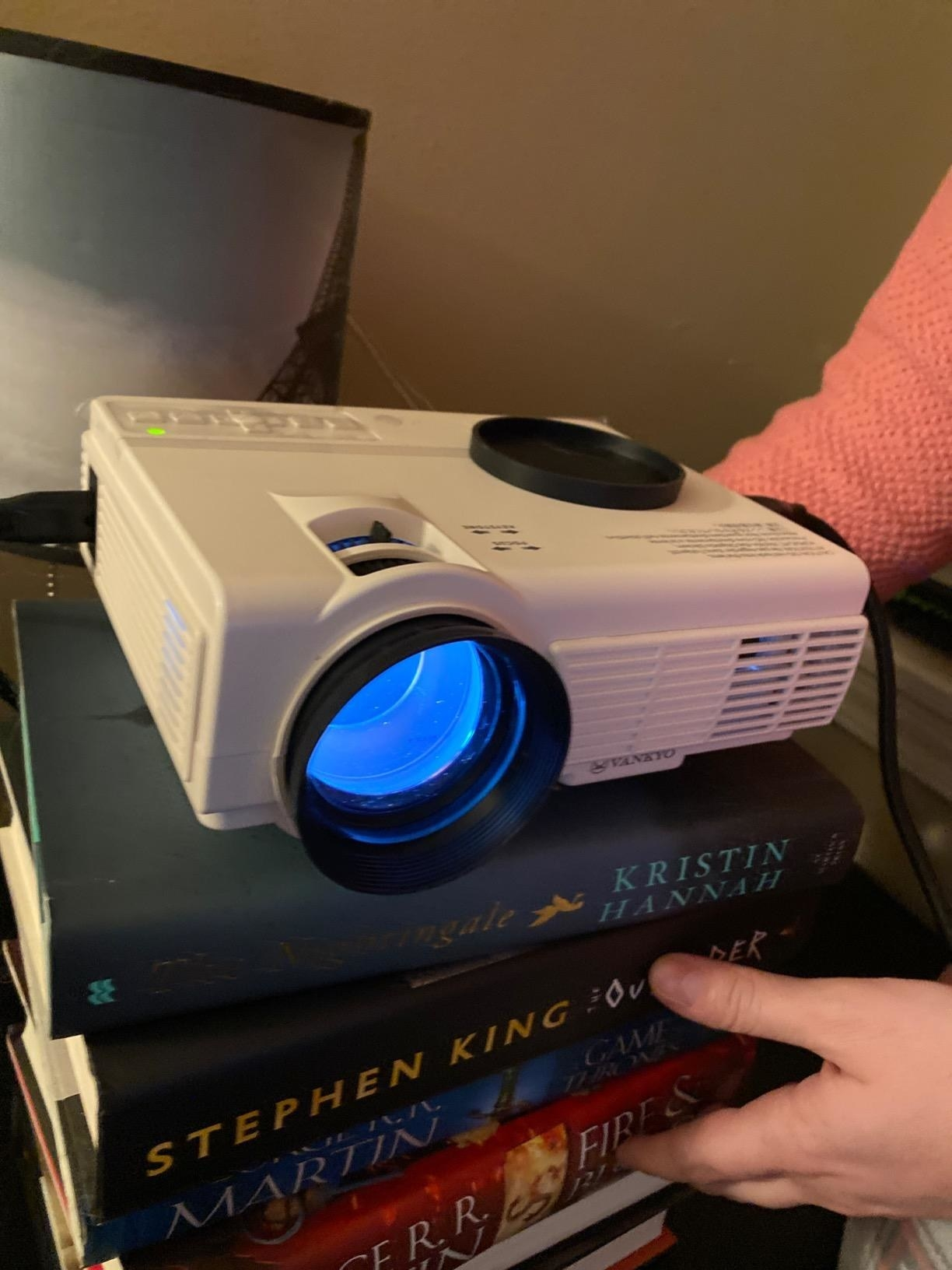 Reviewer photo of projector placed on stack of books
