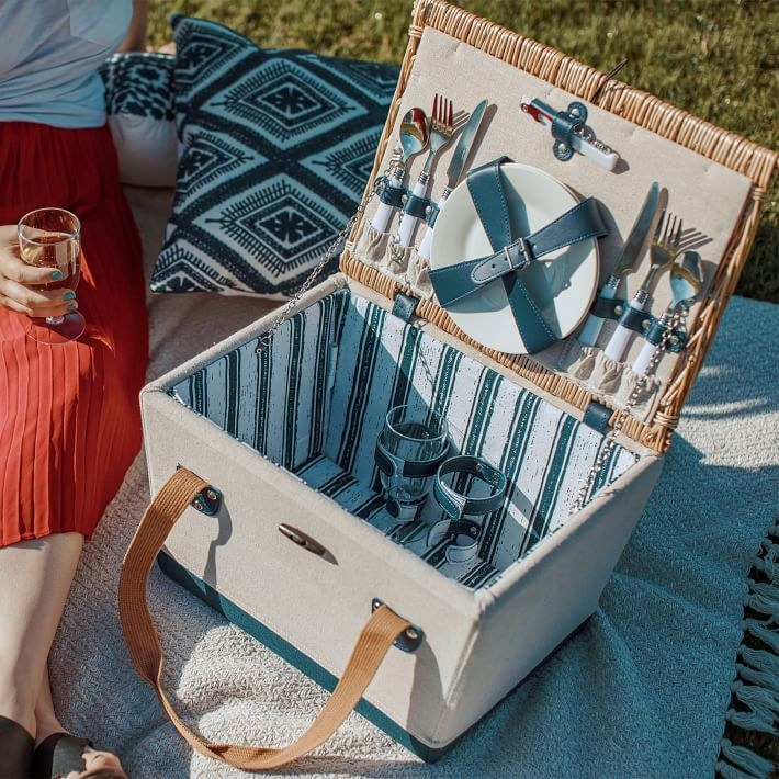 Picnic set opened to reveal plates, wine glasses and utensils