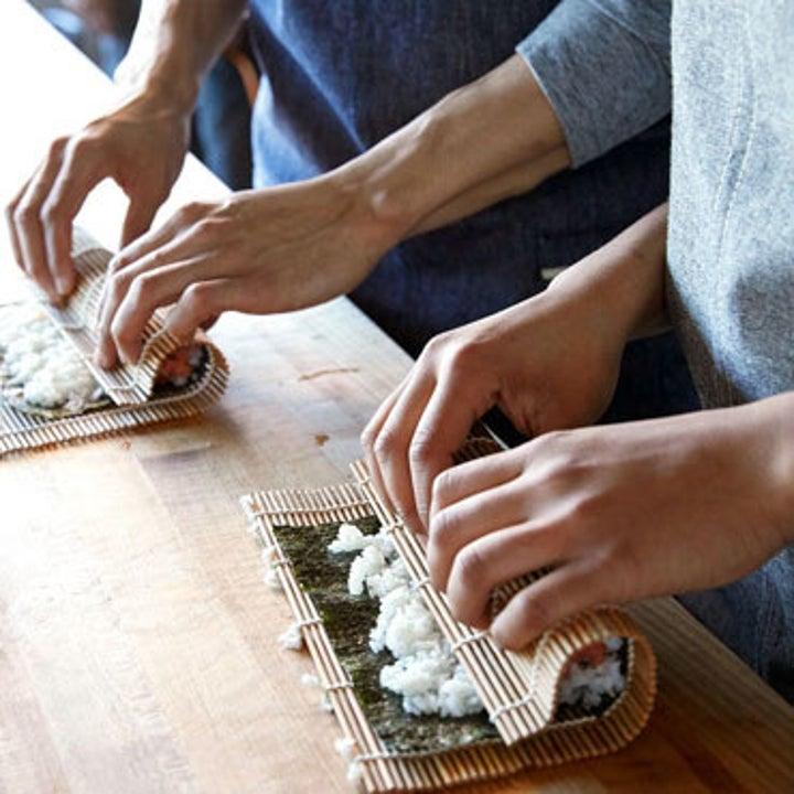 Models rolling homemade sushi