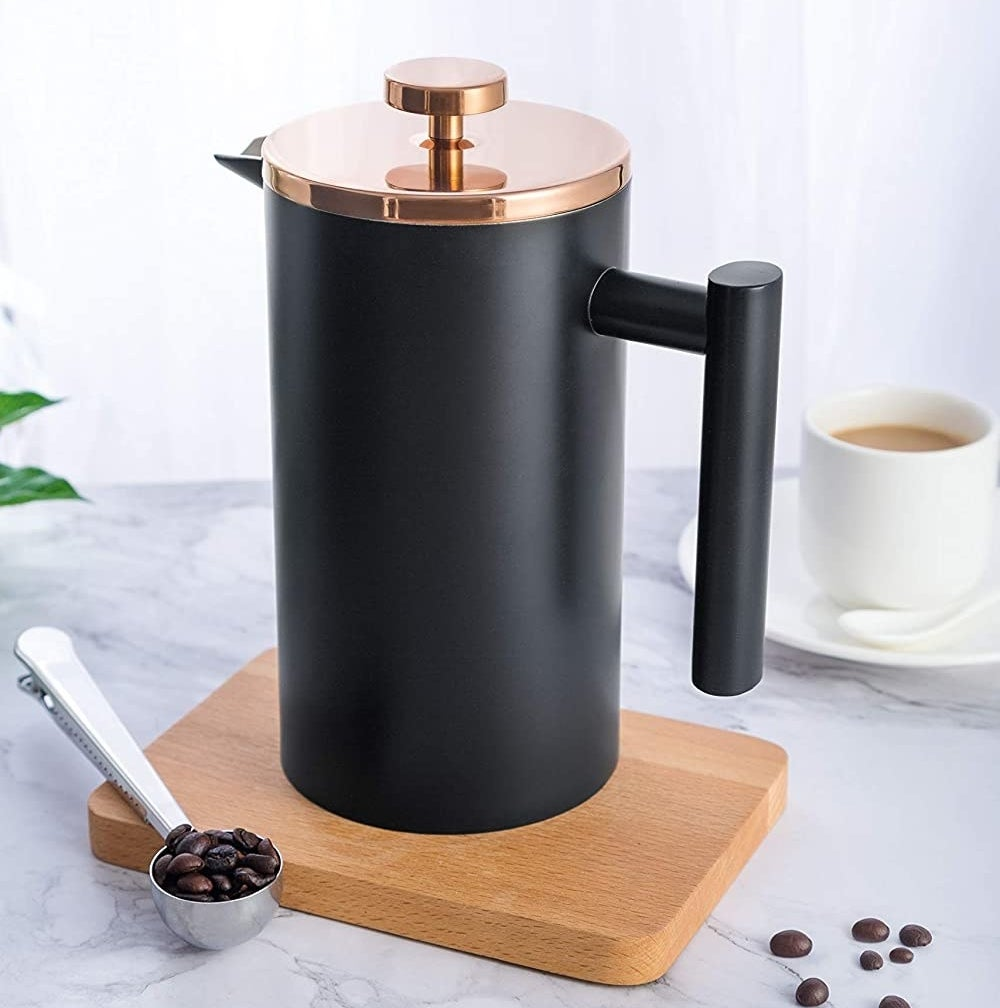 A matte french press on a cutting board