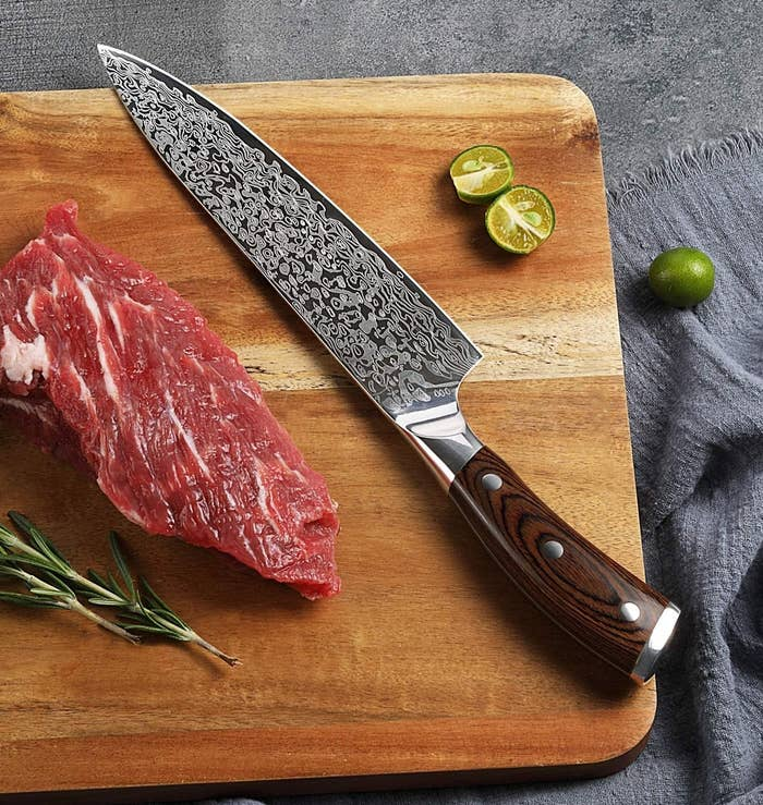 A knife on a cutting board next to a lime, steak, and rosemary