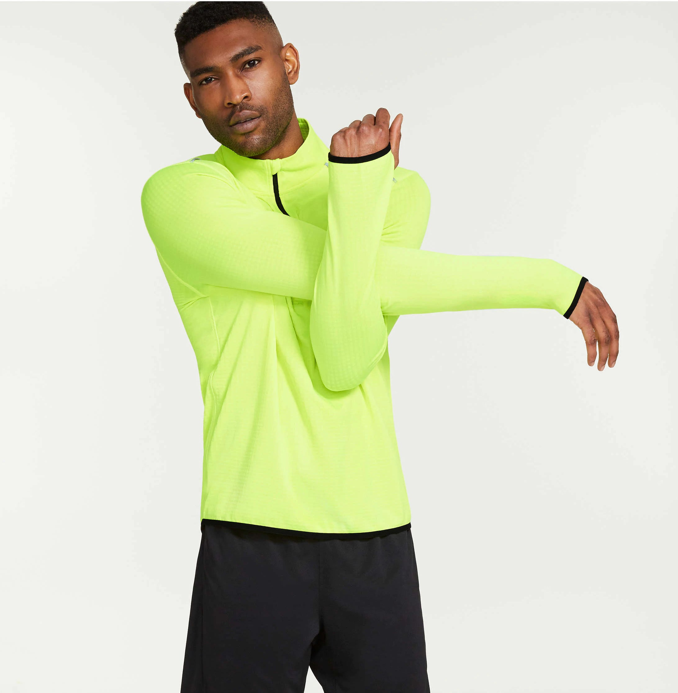 A person wearing a long sleeved neon workout top and shorts