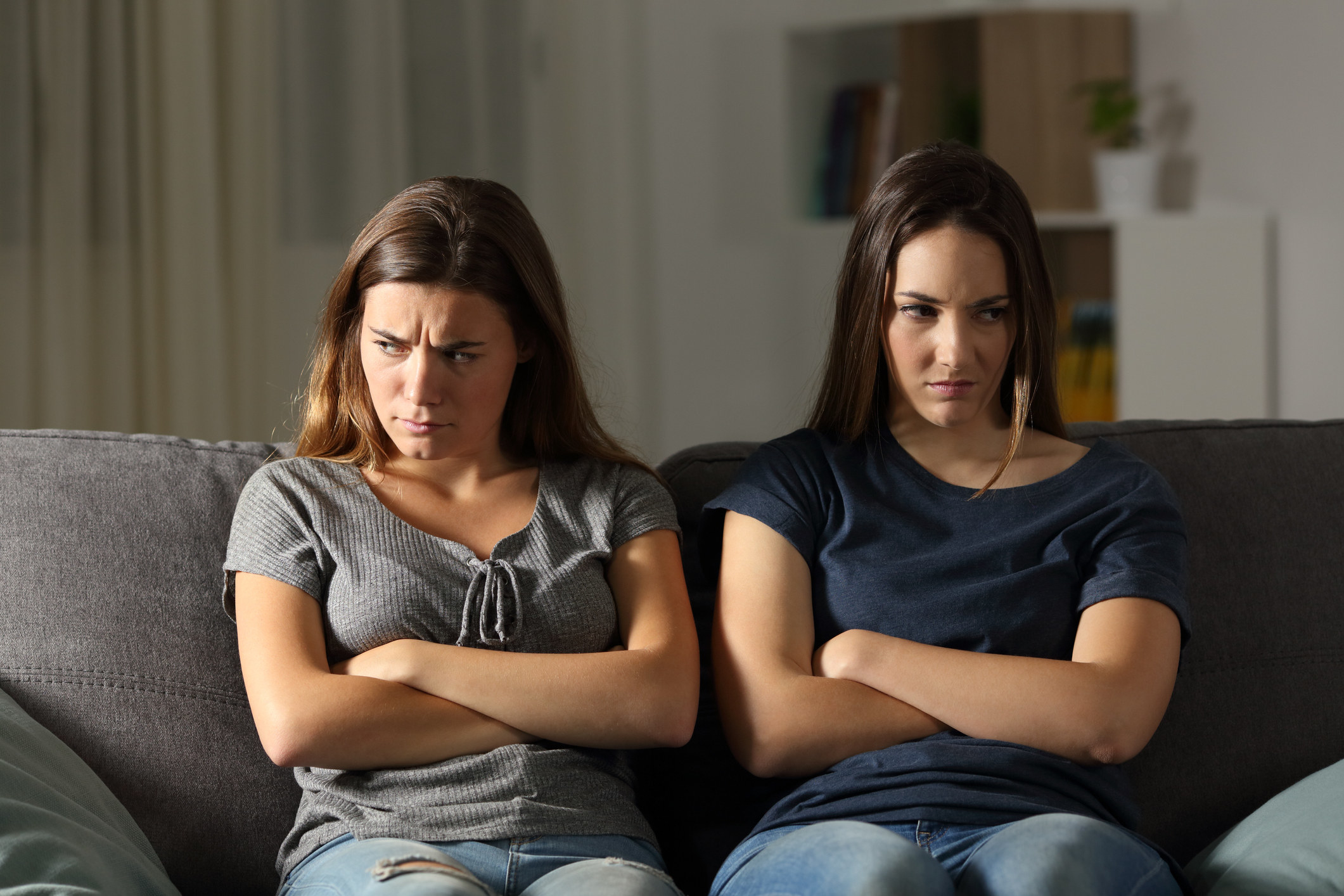 Two angry friends ignoring each other at home while sitting on the same couch