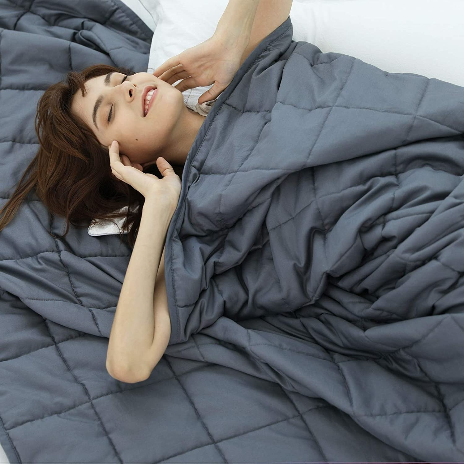 A person swaddled under a weighted blanket