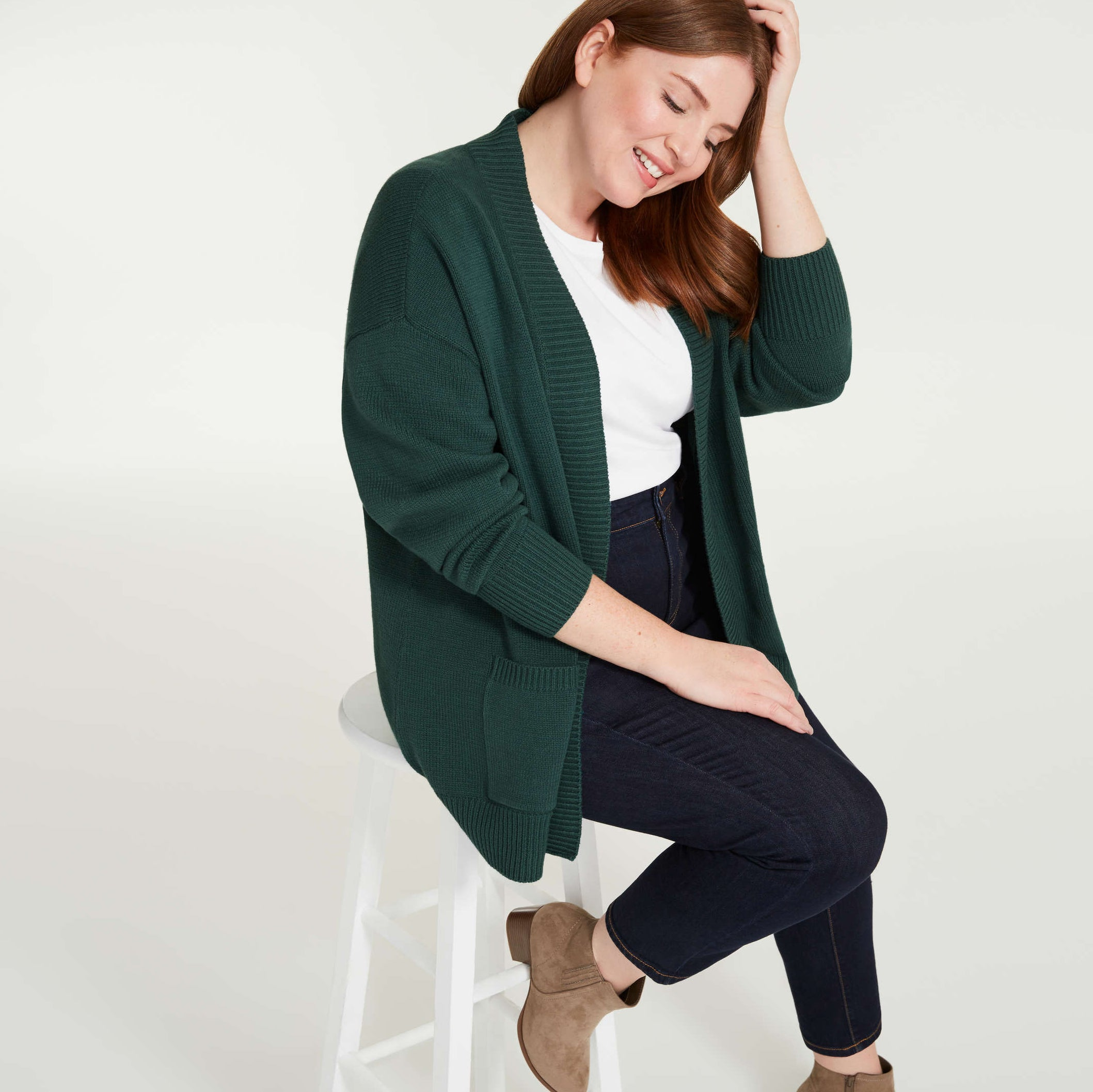 A person wearing a long cardigan over a T-shirt and pants