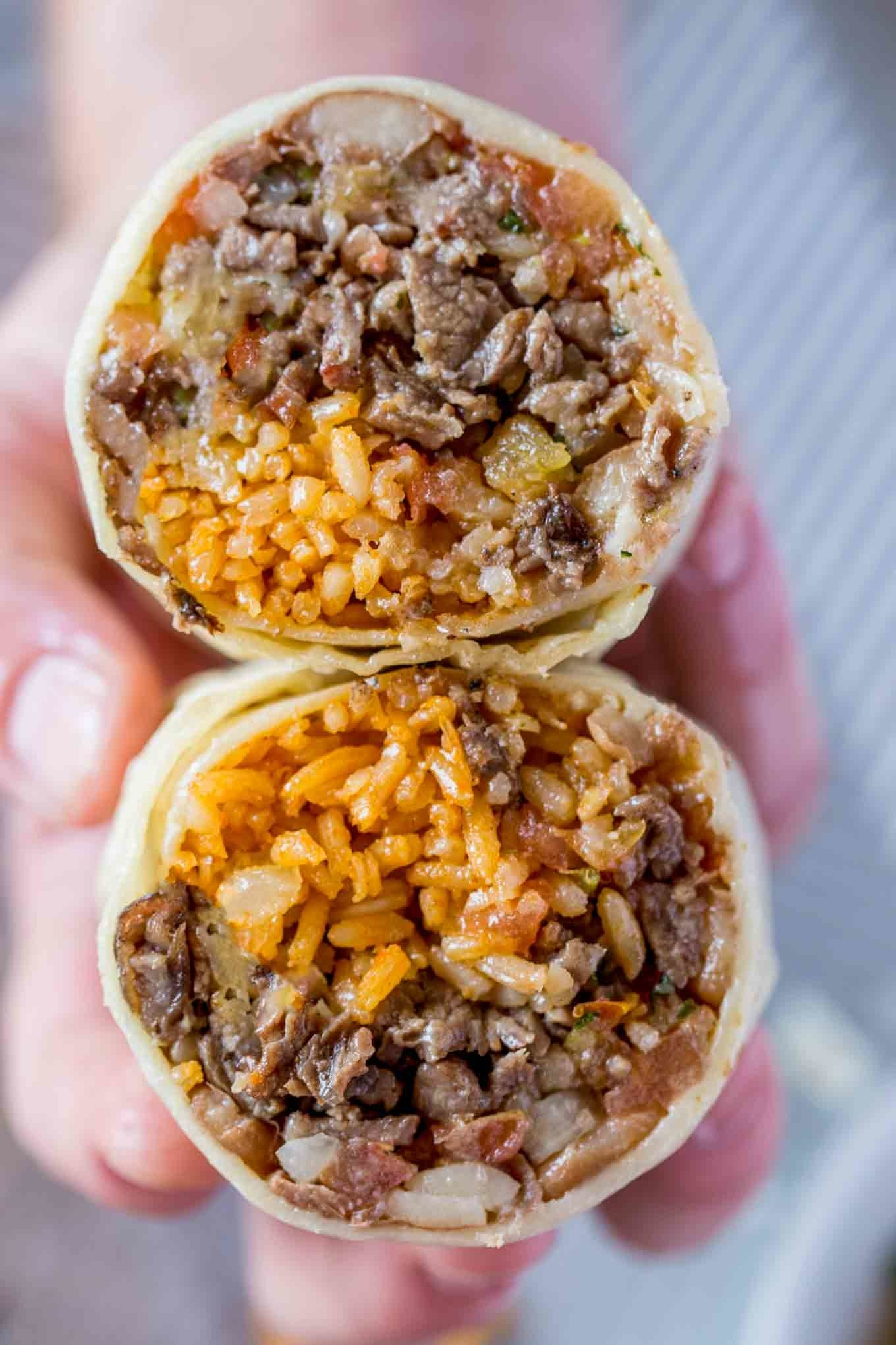 A beef burrito with rice and beans cut into halves.