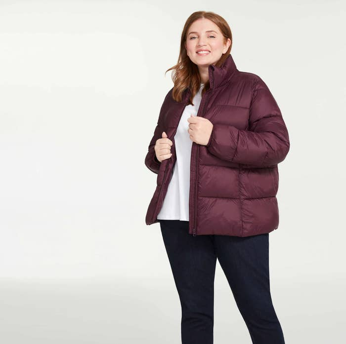 A person wearing a puffer coat over a plain tee and jeans