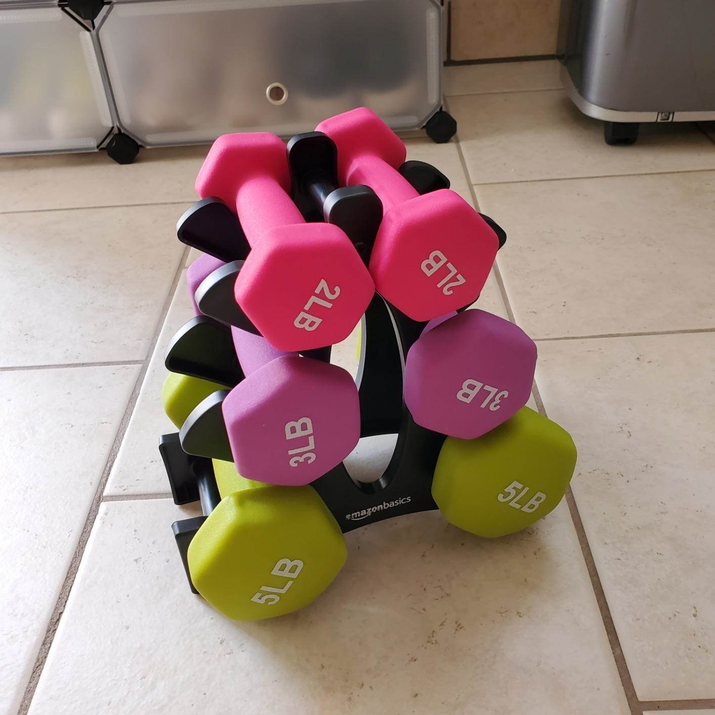 a set of two, three, and five-pound weights sitting on a black stand
