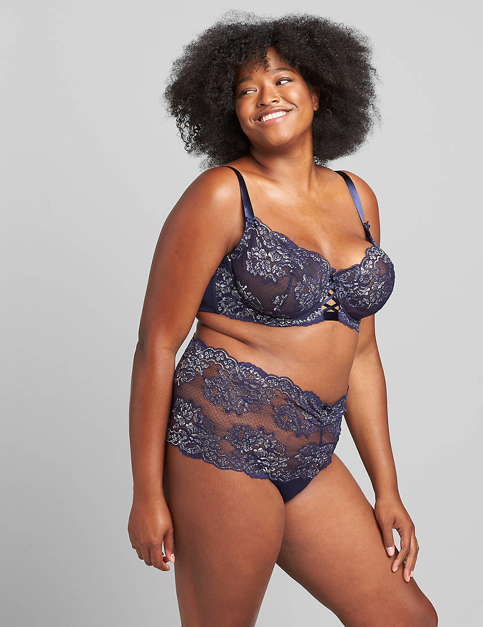 a model in a navy blue matching bra and underwear set with silver lace accents