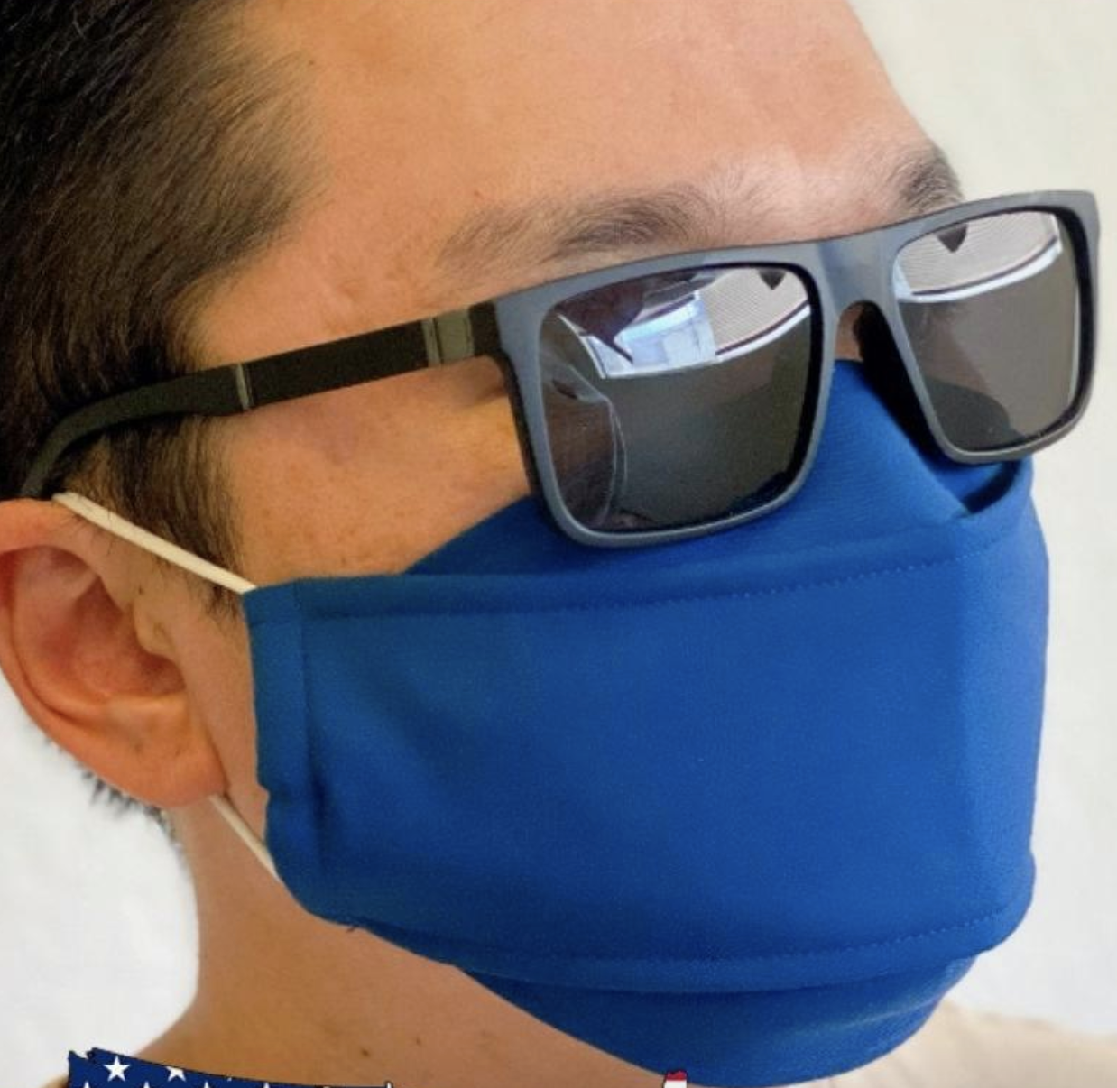 A model in a blue 3D face mask that sits more off the nose wearing a pair of sunglasses