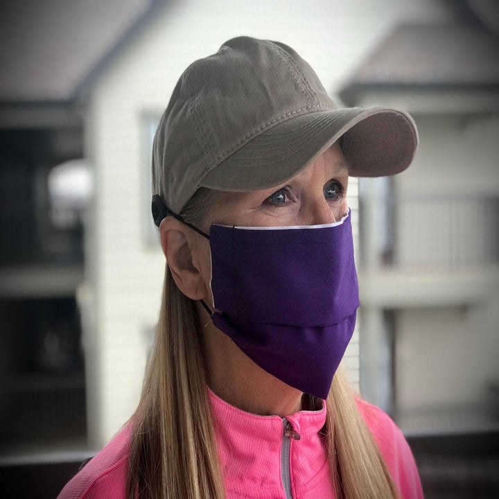 A model in a gray baseball cap with buttons on either side of it hooking a face mask in place