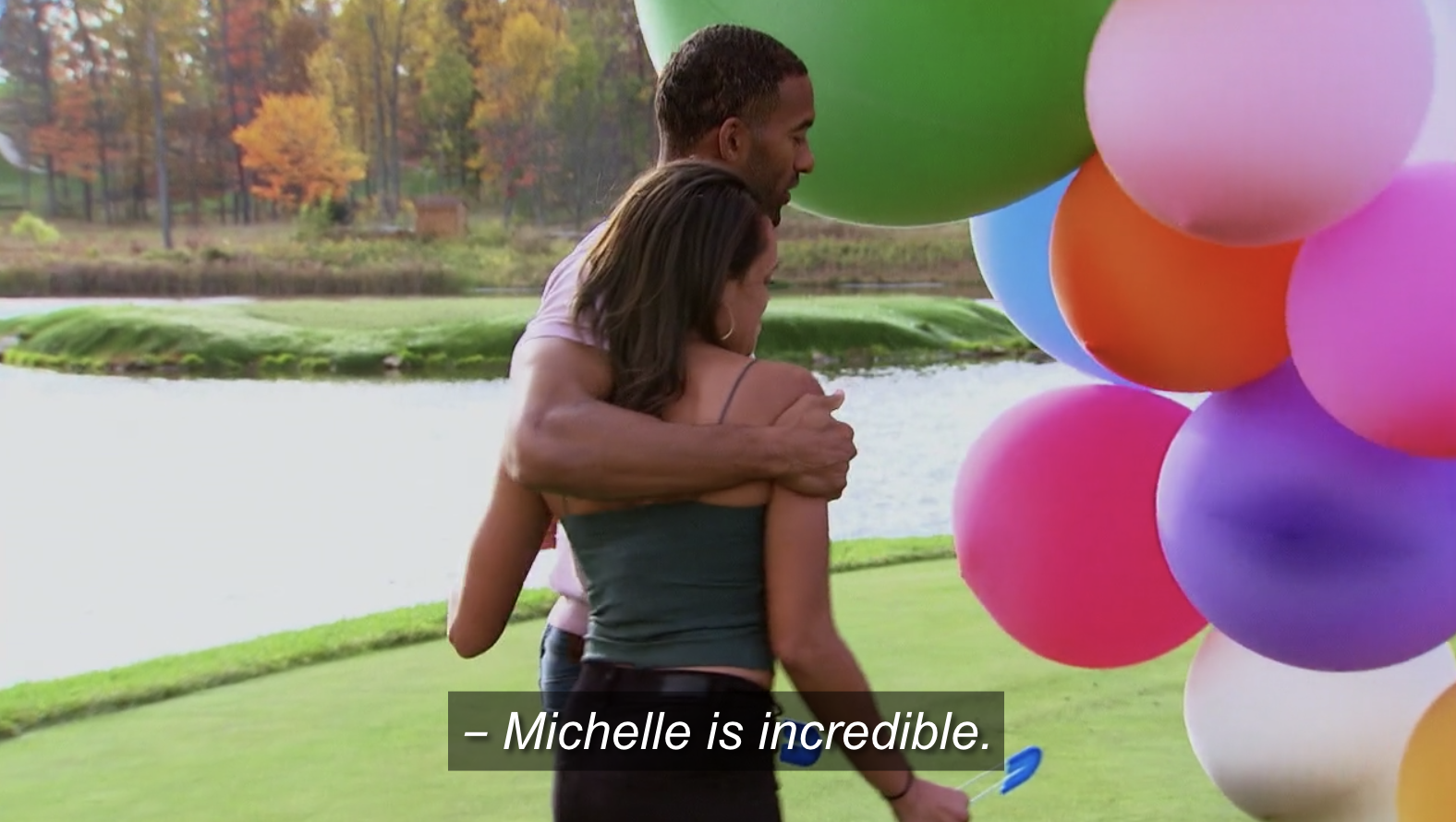 Michelle and Matt James hugging in front of a bouquet of balloons