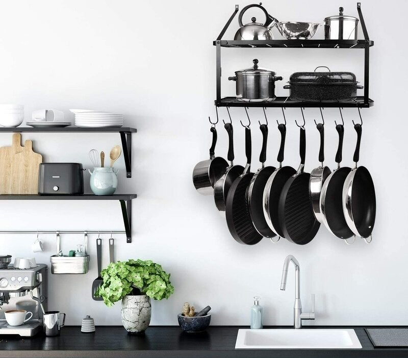 the Wall Mounted Pot Rack on a kitchen wall with pots hanging from the hooks