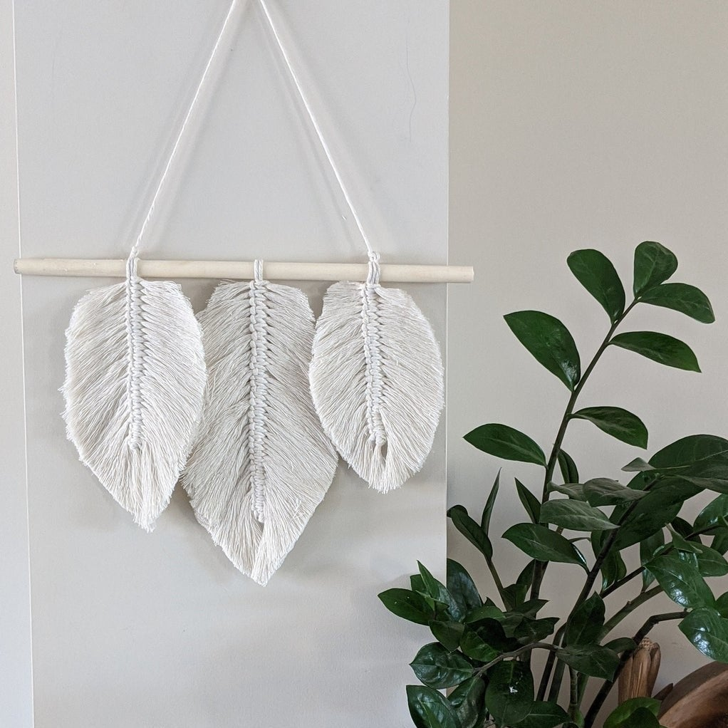 The leaf-patterned macrame hanging on a wall next to a plant