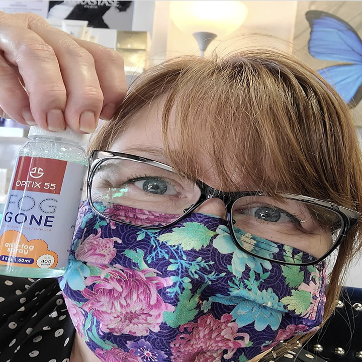 Reviewer holding up bottle of spray with unfogged glasses and face mask on