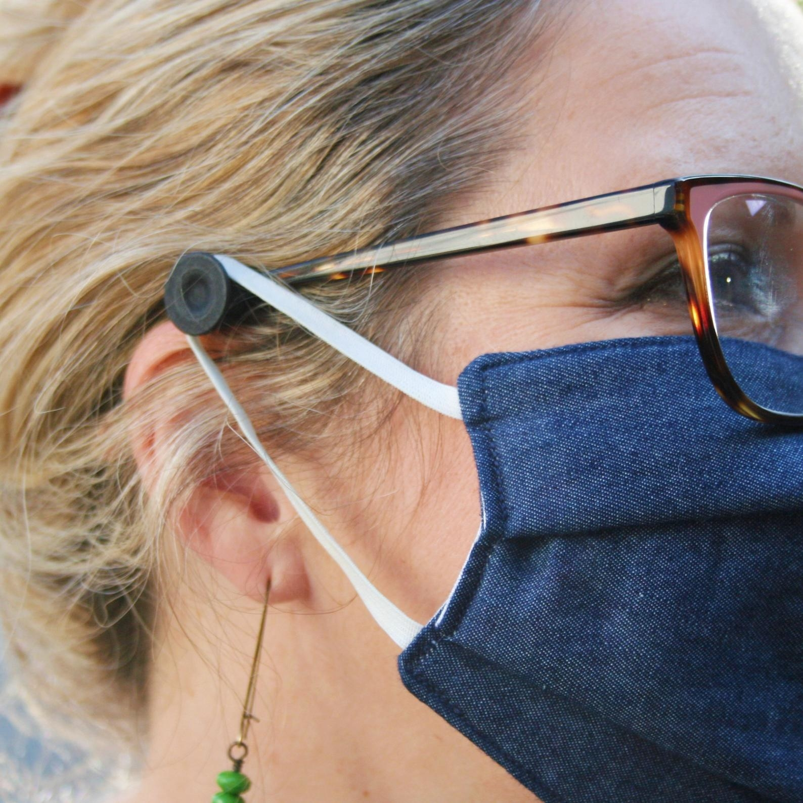 A model with a small black button installed on their glasses just beyond their ear that holds face mask straps in place